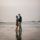 Couple embracing on the beach. Maine engagement photos. Beach engagement photos. Preppy engagement photos.